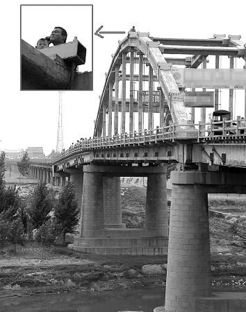 竟然抱着5岁的儿子爬上该市一座二十多米高的大桥拱顶欲跳桥自杀.