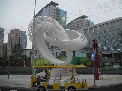 黄色的电瓶车停在雕塑前 奥运官网李方宇摄高清图片