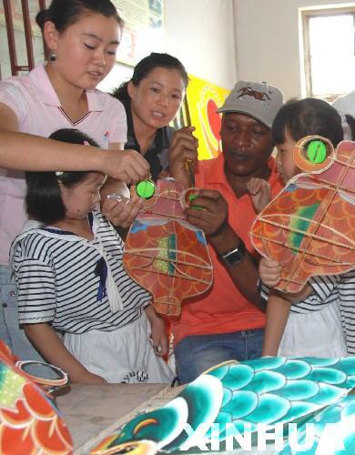 语幼儿园的外籍教师和幼儿园小朋友在中国老师的指导下学习扎制风筝.