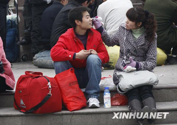 1月30日,将返乡过年的河南商丘人袁冠军(左)在候车时与女友一起分享