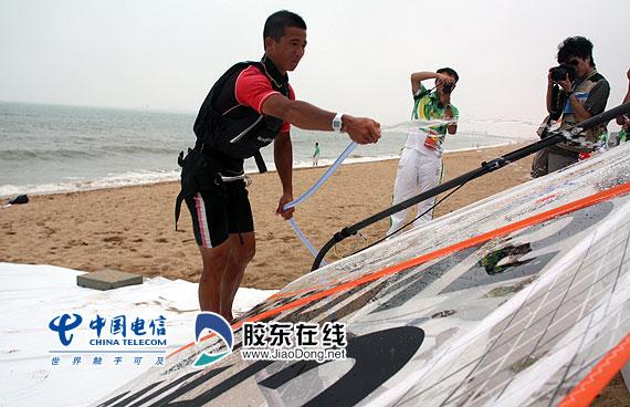中国选手韦必鹏夺冠后冲洗自己的帆板
