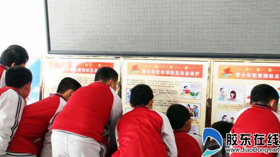 小学生观看法制教育展板