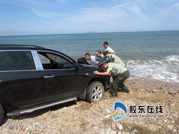 警民合力帮助车主把车推出海滩