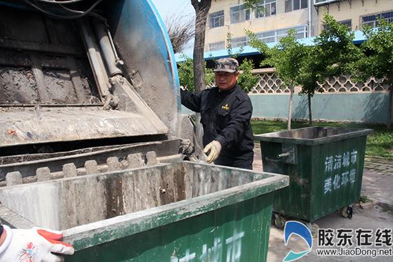 王尤林控制清运车将垃圾箱倾倒干净