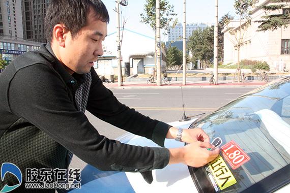 一名出租车司机领到车贴后,立刻为爱车张贴