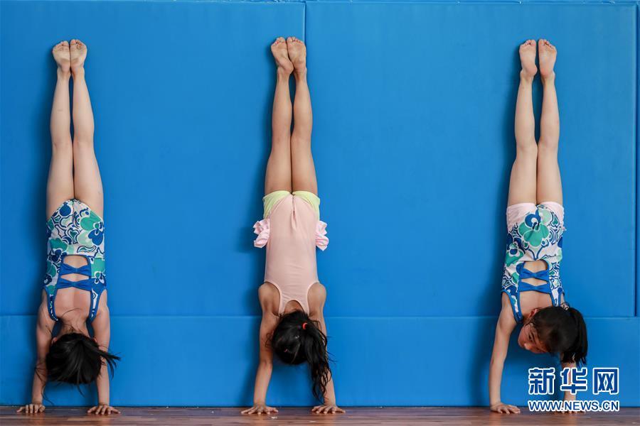 图为小学员龙芊芊(右)与队友在榕江县少年儿童业余体操运动学校内进行体操训练(5月15日摄)。 新华社记者刘续摄