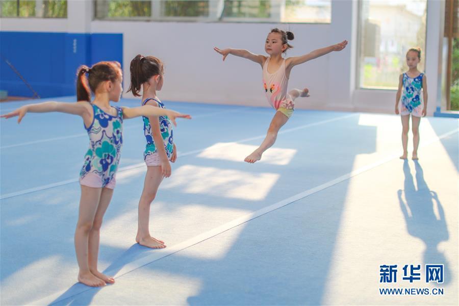 图为小学员徐子涵(右二)在榕江县少年儿童业余体操运动学校内进行体操训练(5月15日摄)。 新华社记者刘续摄