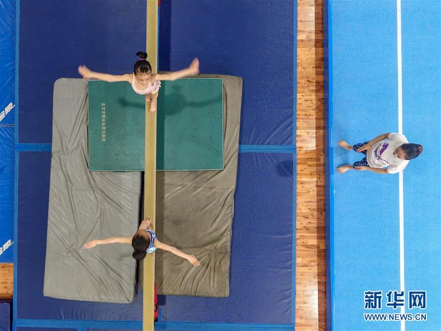 图为小学员徐子涵(左上)在榕江县少年儿童业余体操运动学校内进行平衡木训练(5月15日摄)。 新华社记者刘续摄