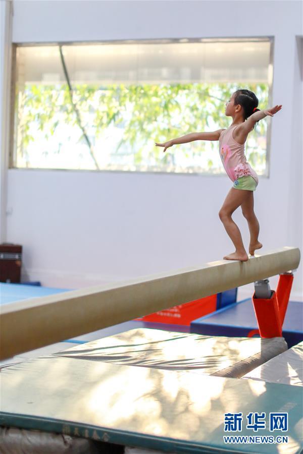 图为小学员徐子涵在榕江县少年儿童业余体操运动学校内进行平衡木训练(5月15日摄)。 新华社记者刘续摄