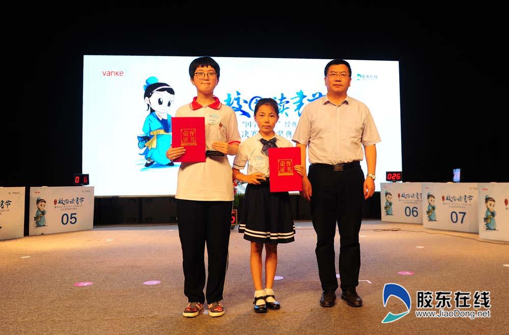 烟台市委宣传部副部长曲波(右一)为为冠军刘耘菲(小学组)、赵晟瑜(中学组)颁奖