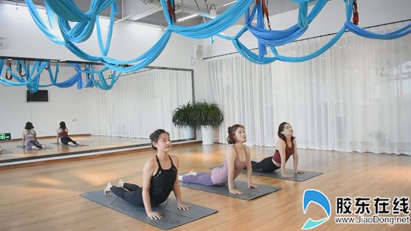 姐妹俩一起跟随教练练习瑜伽