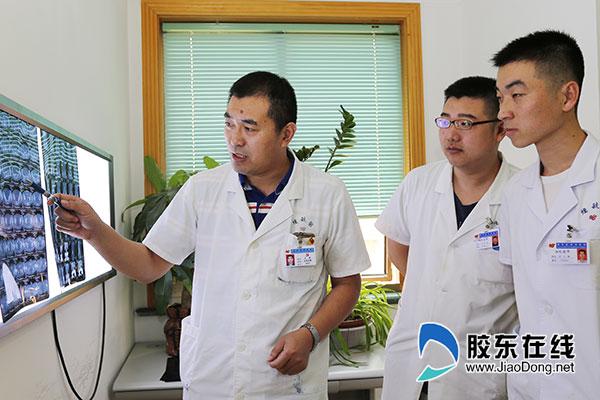 王新(左一)和同事讨论患者病情