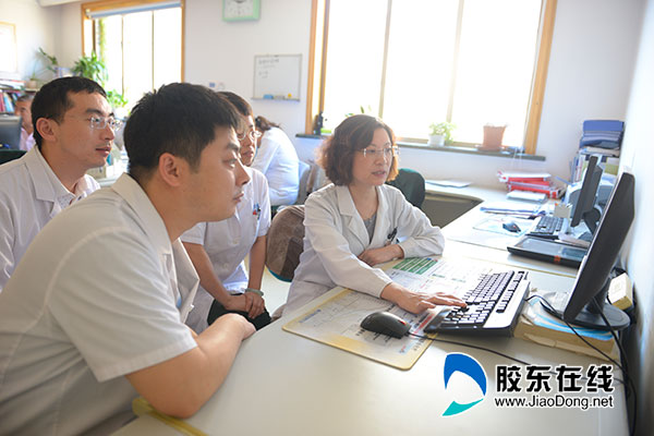 孙萍(右一)与同事讨论病例