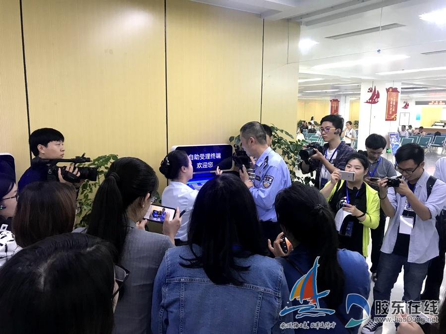 工作人员为采访团成员演示自动受理终端操作