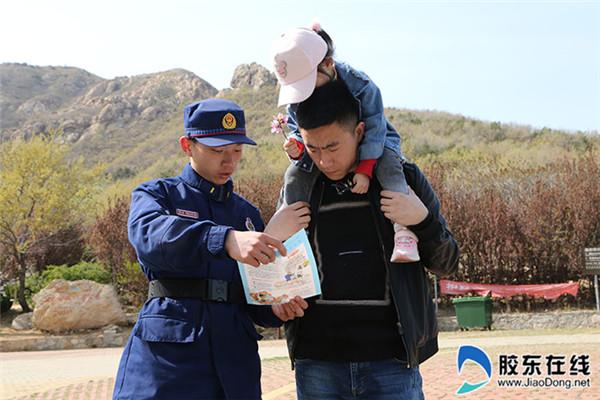 消防队员向爬山的群众宣传消防知识