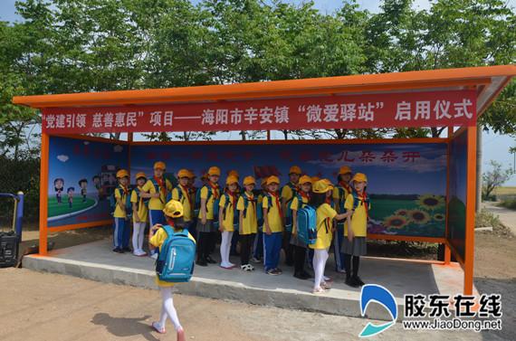 孩子们在爱心候车亭排队等候上车
