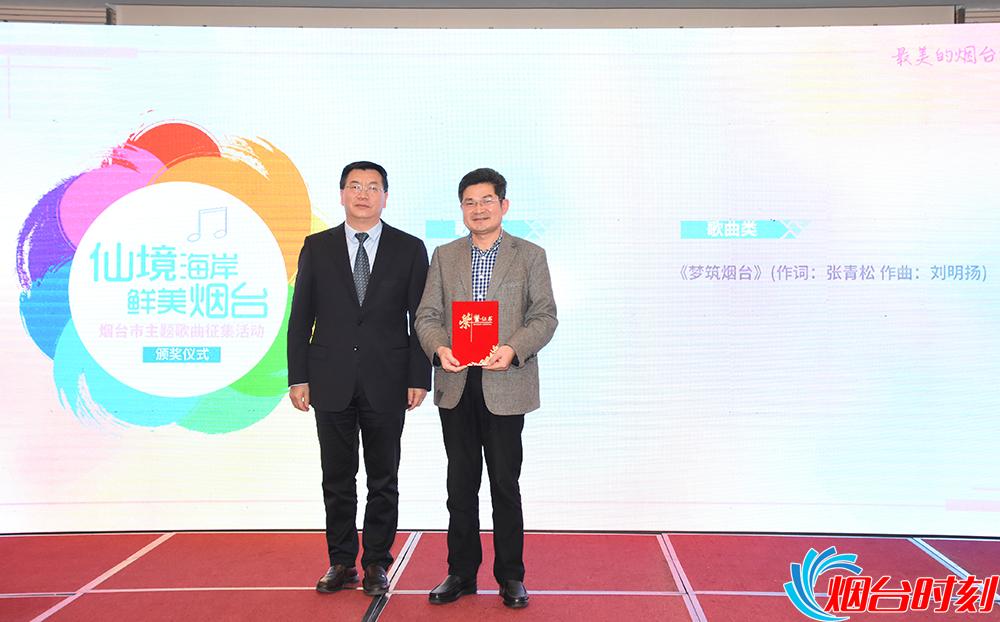 中共烟台市委宣传部副部长 曲波(左)为一等奖获得者(友人代为领奖)颁奖。