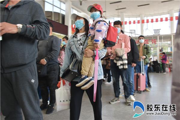 军嫂戴蓉抱着女儿扭扭在蓬长客港排队购票