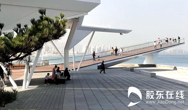 游客在烟台金沙滩后沙广场休闲打卡