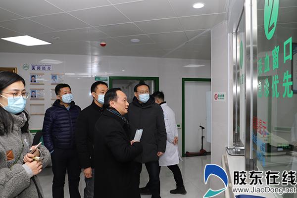 骡坪乡中心卫生院院长卢立早(右二)介绍卫生院改造情况